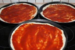 der Teig wird dünn mit Tomatensoße bestrichen
